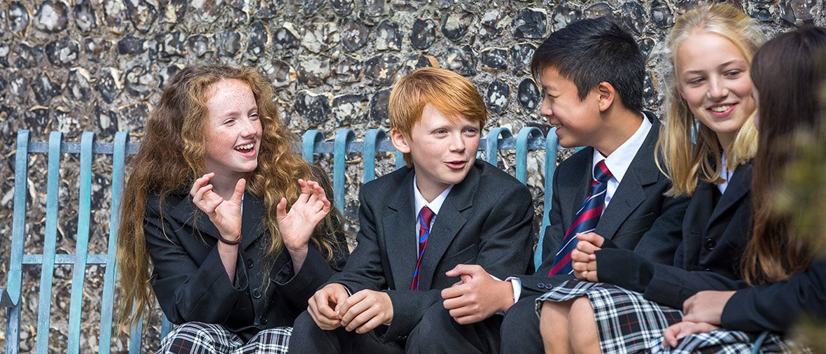 Younger co-ed pupils chatting on bench